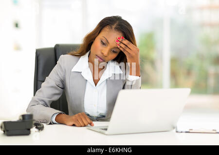 sad African American businesswoman sitting in modern office - Stock Photo