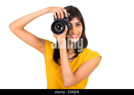 cheerful young Indian woman taking pictures in studio with dslr - Stock Photo