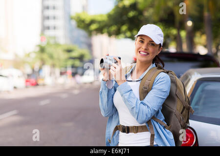 pretty tourist taking pictures with digital camera on urban street - Stock Photo