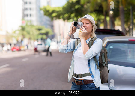 pretty young tourist taking photo in city - Stock Photo