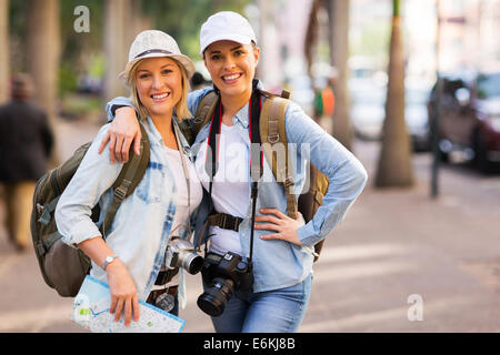 happy two female friends touring together in the city - Stock Photo