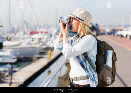 happy tourist taking pictures at the harbour with a digital camera - Stock Photo