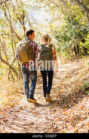 happy young couple walking in autumn forest - Stock Photo