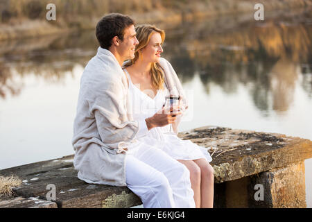 loving couple relaxing on a pier and wrapped in blanket at sunset - Stock Photo