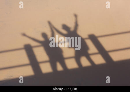 shadow on beach sand of two tourists arms up - Stock Photo