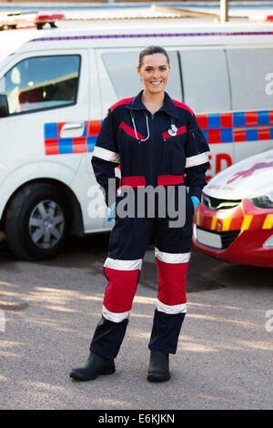 happy emergency medical service worker standing in front of ambulance - Stock Photo