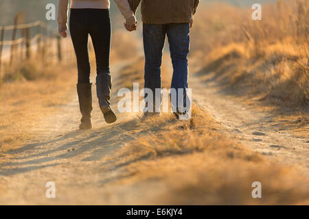 young couple holding hands walking on autumn rural path in the morning - Stock Photo