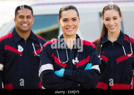 beautiful young EMT with colleagues in front of ambulance - Stock Photo