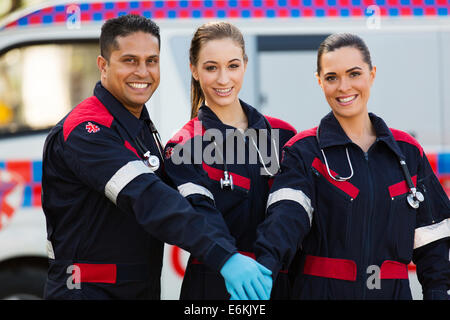 group of paramedics hands together in front of ambulance - Stock Photo