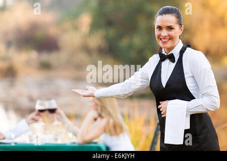 pretty young waitress welcomes customers to romantic dinning environment - Stock Photo