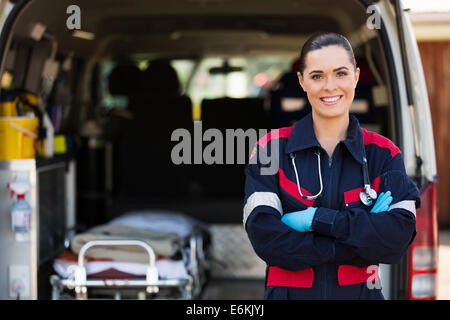 attractive young female emergency medical service worker in front of ambulance - Stock Photo