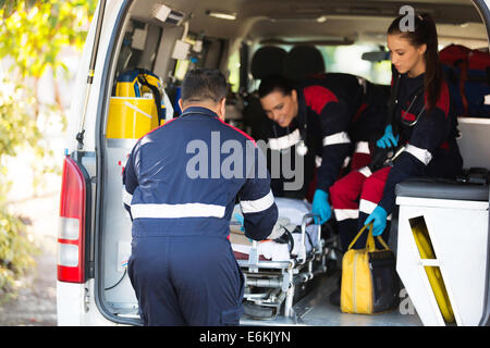 ambulance team pulling a stretcher out of vehicle - Stock Photo