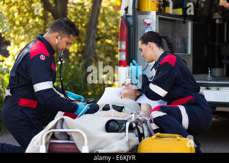 team of paramedics rescuing young patient - Stock Photo