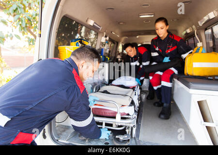 team paramedics taking stretcher out of an ambulance - Stock Photo