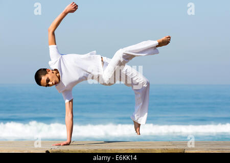 healthy young woman practicing capoeira on the beach - Stock Photo