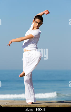 portrait of professional dancer dancing on beach - Stock Photo