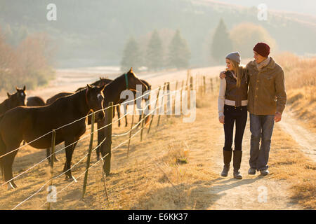 young romantic couple walking in the horse farm - Stock Photo