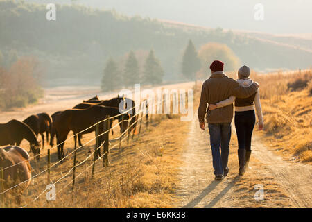 back view of young couple walking in farm road - Stock Photo