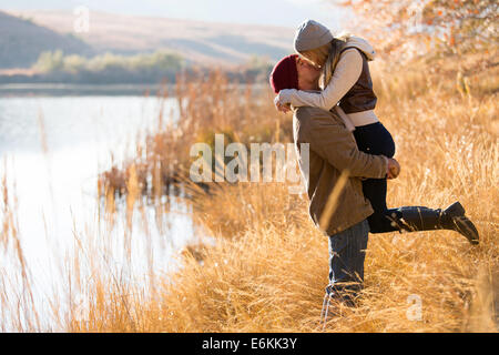 lovely young couple kissing outdoors in autumn - Stock Photo