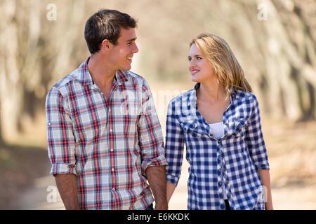 cheerful young couple enjoying a walk in fall - Stock Photo