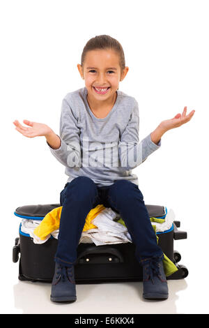 cute little girl sitting on overfilled suitcase - Stock Photo