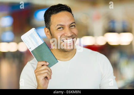 cheerful mid age man holding passport and boarding pass at airport - Stock Photo