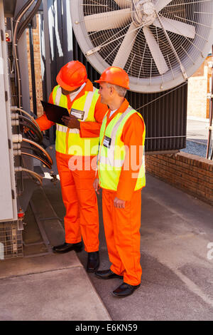 two technicians discussing wiring in substation - Stock Photo