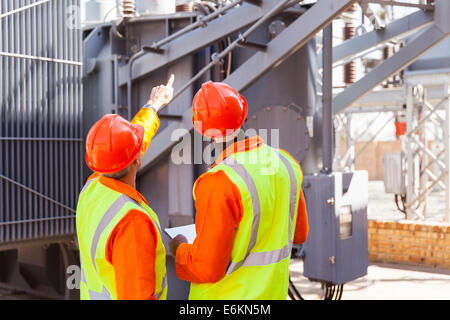 rear view of electrical engineers working in substation - Stock Photo