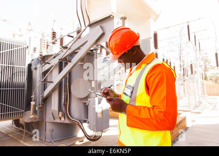 handsome afro American electrical engineer writing on clipboard in power plant - Stock Photo