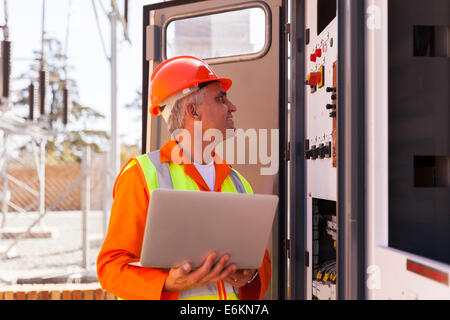 experienced senior electrician working on a transformer in substation - Stock Photo