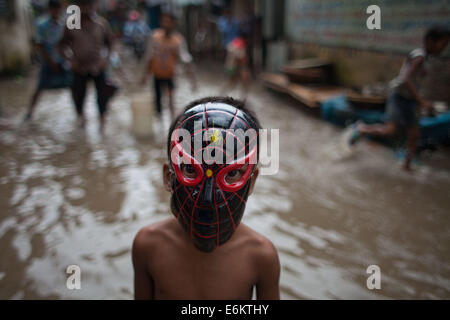 Dhaka, Bangladesh. 26th Aug, 2014. Children wade through the water in a flooded street after a heavy downpour in - Stock Photo