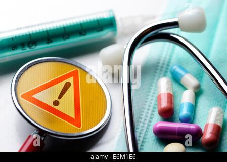 Stethoskop mit Warnschild, Spritze und Tabletten, Symbolfoto medizinischer Behandlungsfehler - Stock Photo