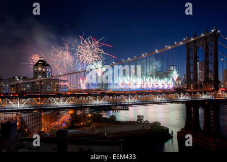 Macy's Fourth of July fireworks seen through Manhattan Bridge, view from Brooklyn rooftop, July 4th, 2014, East - Stock Photo
