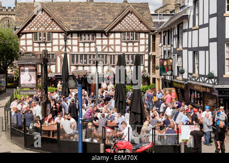 Sinclair's Oyster Bar and 16thc timbered The Old Wellington Inn with crowds of people in busy beer garden outside. - Stock Photo