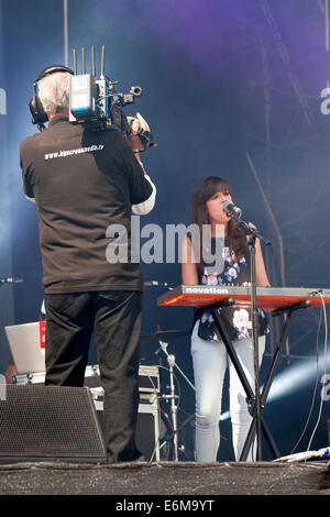 a video cameraman records a female singer performing on stage at the victorious festival 2014 southsea england uk - Stock Photo