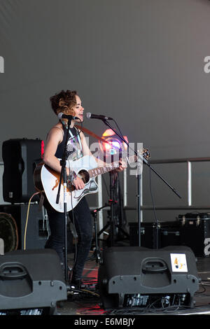 young woman sings and plays acoustic guitar during on stage performance at the victorious festival 2014 southsea - Stock Photo