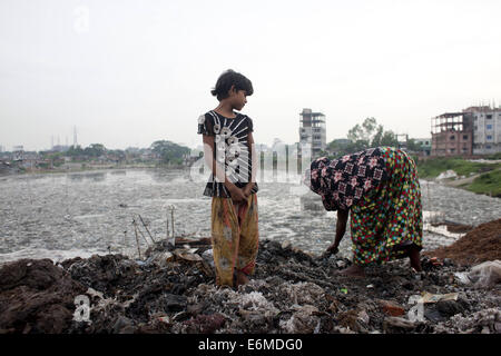 Dhaka, Bangladesh. 26th Aug, 2014. A woman collects objects from the wastage leather material in open space at the - Stock Photo
