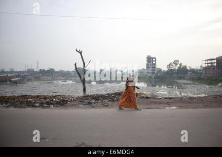 Dhaka, Bangladesh. 26th Aug, 2014. A woman passes the open dumping place of wastage lather materials at the highly - Stock Photo