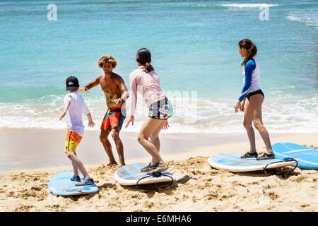 Hawaii Hawaiian Honolulu Waikiki Beach Sans Souci State Recreational Park Pacific Ocean man boy girl surfing lessons - Stock Photo