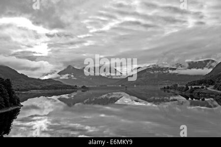 Early morning mist rising from the Glencoe mountains, reflected in Loch Leven, Lochaber, Scottish Highlands, Scotland - Stock Photo