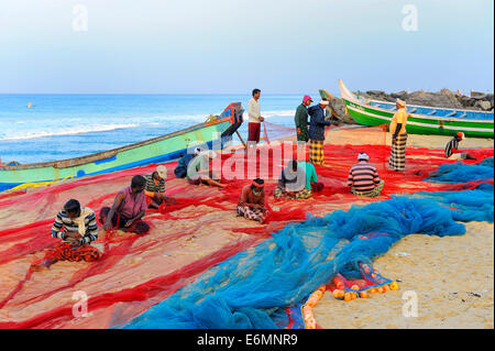 Fishermen repairing nets on the beach, Arabian Sea, Varkala, Kerala, South India, India - Stock Photo