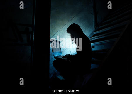 Female computer hacker sitting with a laptop in the dark, in an old building - Stock Photo