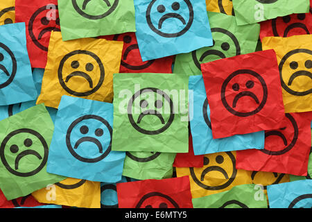 Colorful crumpled adhesive notes with sad faces. - Stock Photo