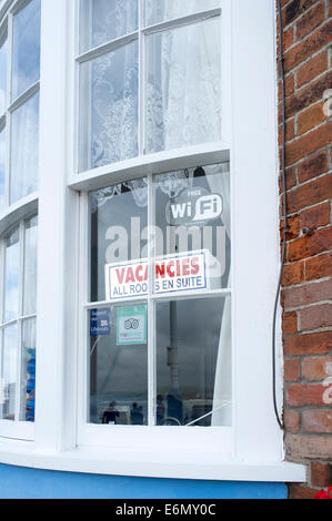 Vacancies, Trip advisor and WiFi signs in bed and breakfast hotel window Weymouth Dorset UK - Stock Photo