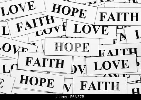 Pieces of paper with the words 'Faith', 'Hope' and 'Love'. - Stock Photo