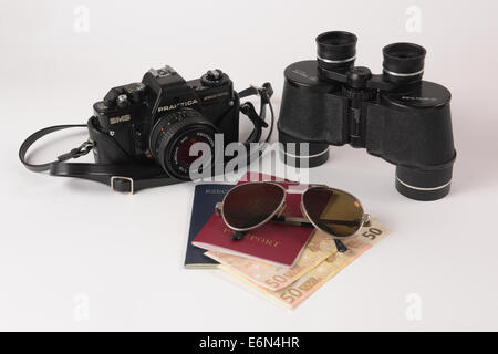 Old analog camera, binocular, sunglasses and passports with some money. - Stock Photo
