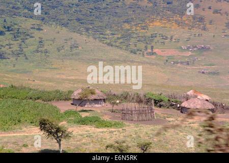 A small Maasai village composed by four huts between Ngorongoro Crater and Serengeti Plains, Tanzania. - Stock Photo