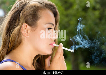 young woman smoking cigarette outdoors - Stock Photo
