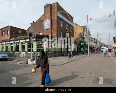 Woman walking by The Chequers pub in Walthamstow High Street, London  E17 UK KATHY DEWITT - Stock Photo