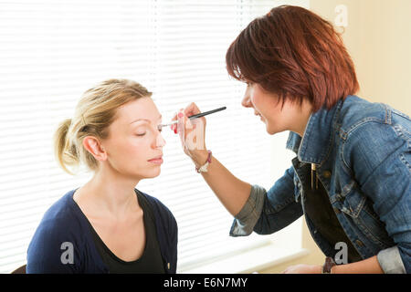 makeup artist applying cosmetics to a young model / actress - Stock Photo